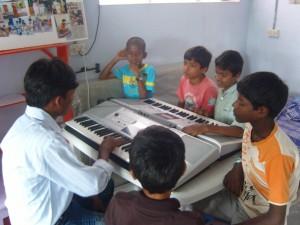 de kinderen maken kennis met Praveen, de muziekstudent die keyboardles komt geven