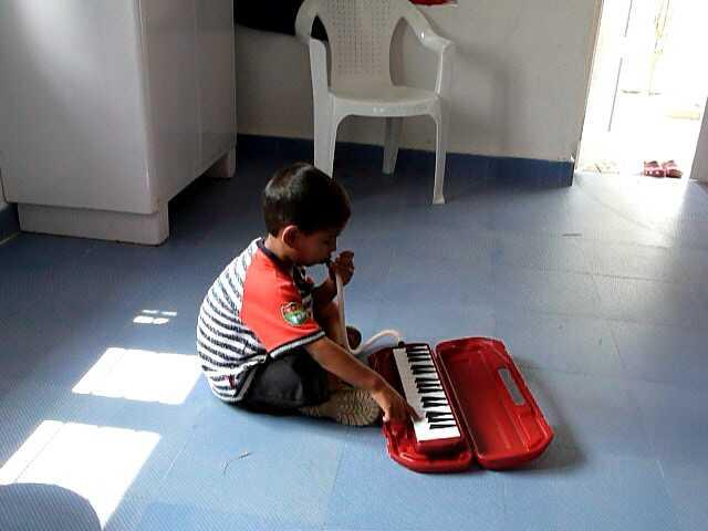 Ali, 4 jaar, vorig jaar op het station gevonden, verdiept in de melodica.